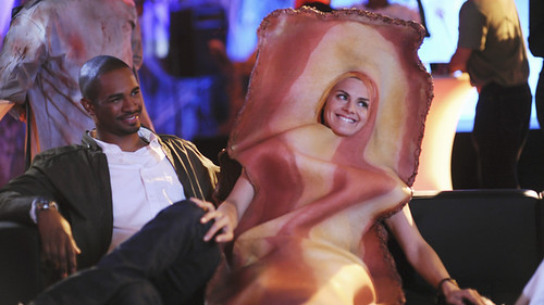 Brad, a black man, and Jane, a white woman, sit on a couch. Jane is wearing a bacon costume.