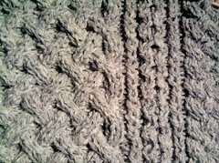 A detail of the cable pattern in a gray Aran style sweater