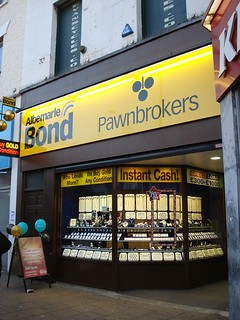 "A small shopfront with a curved display frontage holding various items of jewellery. A sign above reads ""Albemarle Bond Pawnbrokers"" in black text on a yellow background, with a stylised pawnbrokers' ""three balls"" logo. An A-board with balloons tied to it is on the pavement outside. On the first floor, window blinds read ""evanscycles.com""."