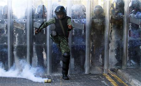 Riot policeman in Maldives kicks a teargas cannister thrown back at him by people protesting in the streets. The president was forced from office at gunpoint leaving the South Pacific state in political turmoil. by Pan-African News Wire File Photos