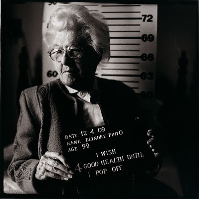 Black and white mugshot-style photo of a white woman aged 99. The placard she's holding says I wish for good health until I pop off