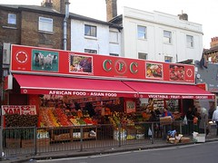 """The same shop as in the first photo in this article, but stretching over two shopfronts instead of one.  The awning is longer here, and in addition reads """"Vegetable — Fruit — Bakery — Grocery"""".  There still seems to be a division between the two shops, at least at the front, where groceries line the wall in between."""