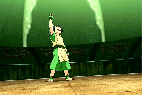 Toph standing in the middle of an empty fighting square. She triumphantly holds her fist in the air as the winner. She is wearing her typical outfit: barefoot, a green tunic with a tan tunic belted over it.