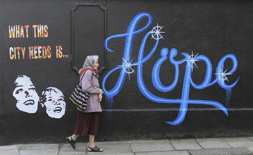 A woman walks past a wall covered in graffiti, which reads 'What This City Needs Is Hope' on a building in Dublin, Ireland.