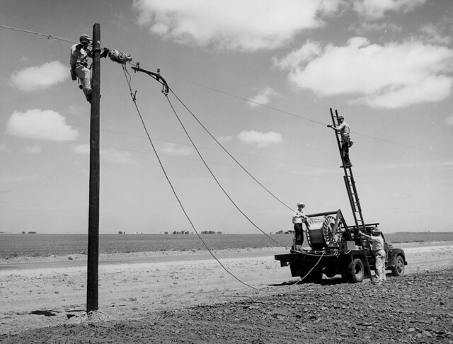 Rural Electrification Administration workers erect telephone lines in rural areas.