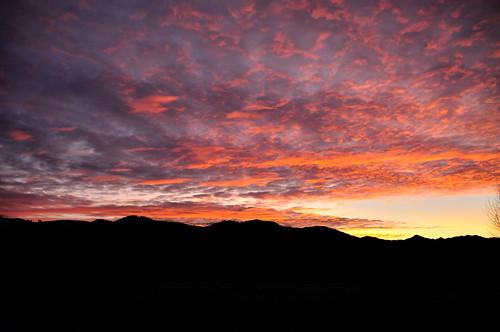 pink winter sky orange snow mountains beautiful yellow clouds sunrise dawn washington winthrop hills methowvalley