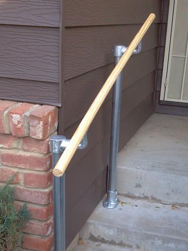 Handlauf aus Holz bei einem Rohrverbinder-Geländer