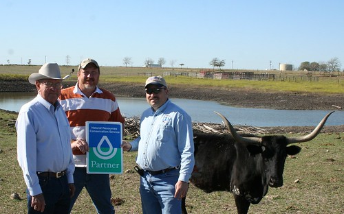 Milton Koenning with Fayette SWCD, Glen Minzenmeyer with NRCS present David Brooks, with a NRCS cooperative partnership sign for his conservation efforts on the DDV Ranch in Fayette County.