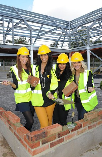 The Saturdays lay bricks at new hospice site