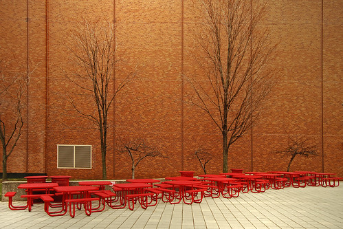 seventeen red metal picnic tables awaiting the snow