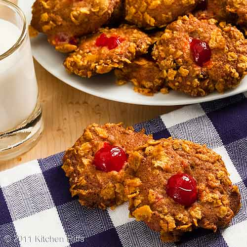 Cherry Winks cookies on napkin with plate of cookies and milk in background