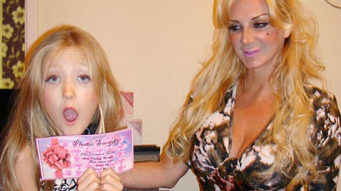Poppy, a blond white girl, holding a plastic surgery voucher. Her mother, a blond white woman, stands in the background