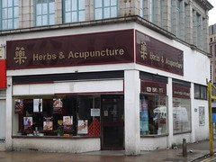 "A corner shopfront with a sign above reading ""藥 [Chinese character for 'medicine'] Herbs & Acupuncture"". Posters in the window feature various smiling people and health claims."