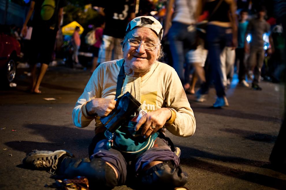 Un hombre discapacitado físicamente pero animado en espíritu saluda y agradece a los transeúntes que le dejan monedas en su jarra. Actos de caridad por los hermanos discapacitados son frecuentemente vistos en esta festividad. (Elton Núñez)