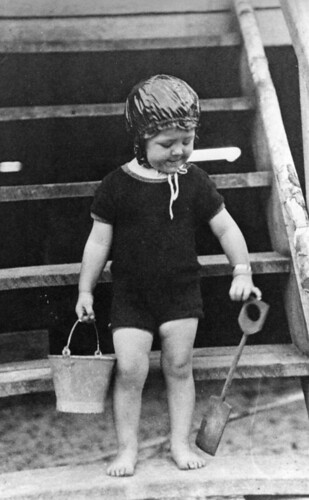 Young child in swimming costume with bucket and spade
