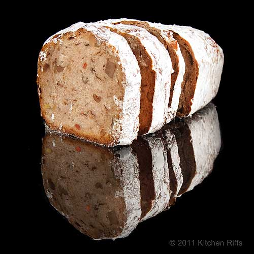 Stollen loaf and slices reflected on black acrylic