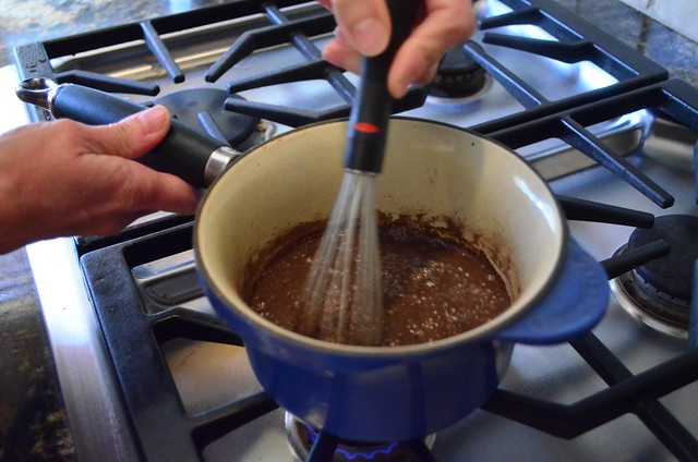 Saucepan with the mixture added along with cocoa powder, while being whisked.