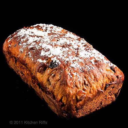 Stollen loaf with powdered sugar, black background