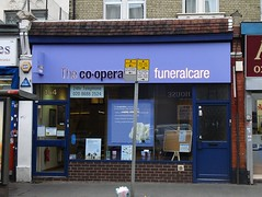 "A small terraced shopfront with a brick riser and surround painted in dark blue and light purple.  Various posters are in the central window, above which is a sign reading ""The co-opera[obscured] funeralcare""."