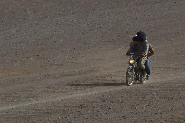 Moto atravesando la tormenta de arena con turbantes