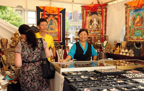 Happy merchants, statues, jewelry, Tibetan thangkas of Medicine Buddha, White Tara, Lord Buddha, offering cups, White tent market, Happy Birthday to His Holiness the Dalai Lama Peace Parade, Tibetans at Kalachakra, Washington D.C., USA by Wonderlane