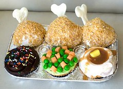 six cupcakes in the shape of tv dinner items like drumsticks, mashed potatoes, and peas and carrots