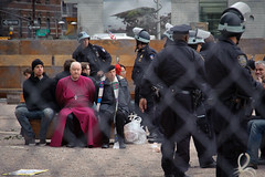 OWS briefly takes Trinity Church lot. Bishop George Packard one of first over fence & of around 50 arrested
