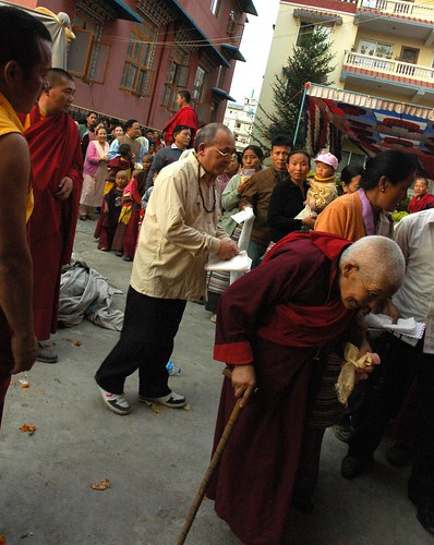 Not to notice the disabled is cultural. Tibetan culture notices: an elderly nun walks towards the stage to receive the long life blessing, with everyone watching her out of respect, Tharlam Monastery Courtyard, Boudha, Kathmandu, Nepal by Wonderlane