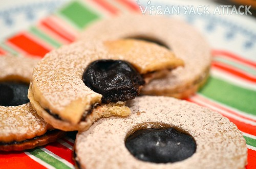 Chocolate linzer cookies stacked together on a holiday napkin