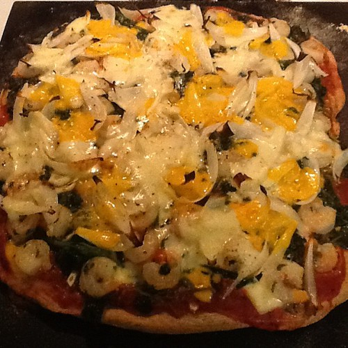 homemade wheat and basil crust pizza topped with shrimp, spinach, onion, garlic, and two cheeses.
