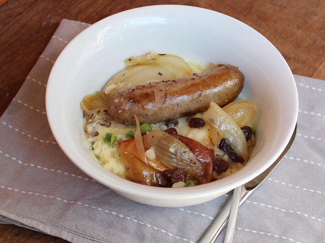 Baked sausages with apples, onion, raisins and cider