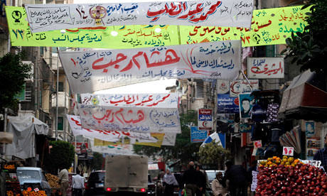 People walk through Alexandria, Egypt amid election banners. Unrest has swept the country since November 19 demanding an immediate end to military rule. by Pan-African News Wire File Photos