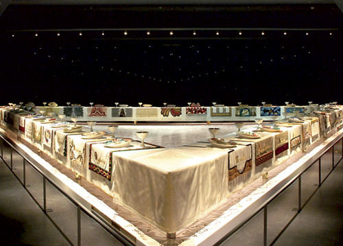 Judy Chicago's Dinner Party, a table in a large gallery space set with many different place settings