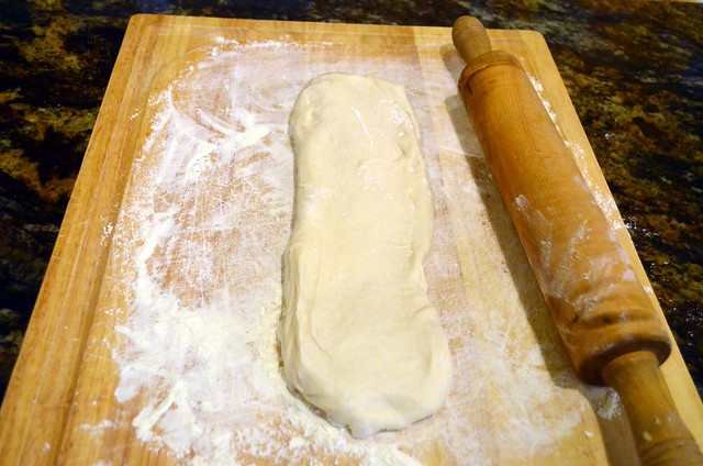 A cutting board with flour, a rolling pin and thawed bread dough on top.