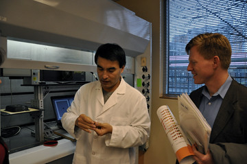 The Food Innovation Center's Dr. Quingyue Ling shows USDA's Max Finberg how new technology can laser-imprint tracking data on individual food items as small as a grain of rice at the center's Radio Frequency Identification Lab.