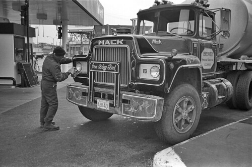 Truck driver cleans headlights at gas station, Allston