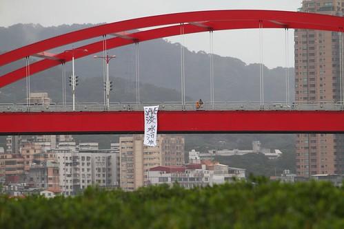 反對新建淡北快速道路,環團在關渡大橋垂下七公尺長「Save淡水河岸」的巨型抗議布條照片。綠色公民行動聯盟提供。