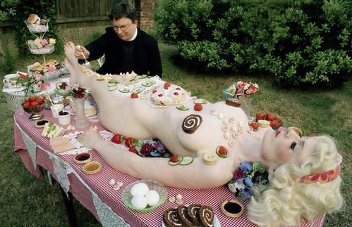 nude white woman on a picnic table covered in snacks. A priest is serving himself some of the snacks
