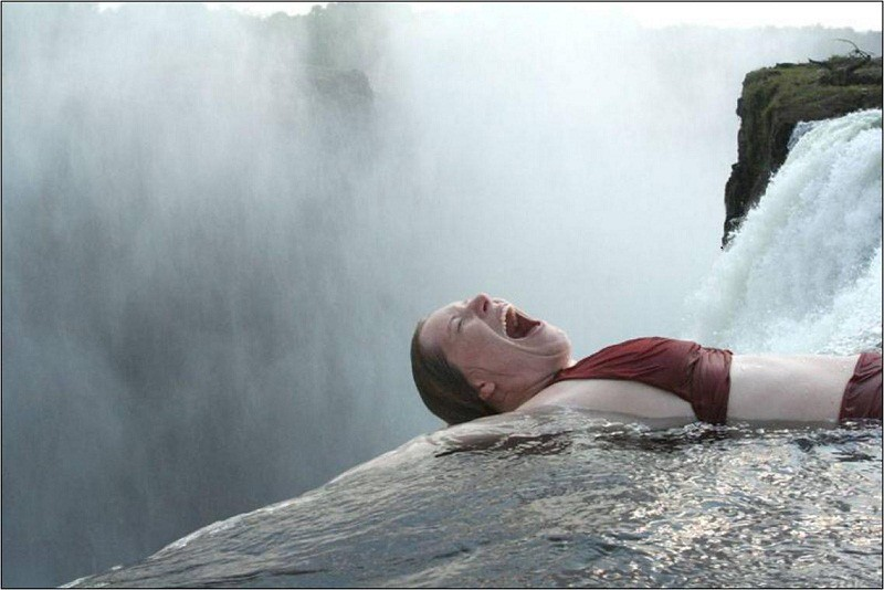 ヴィクトリアの滝のデビルズプールの絶壁で叫ぶ観光客