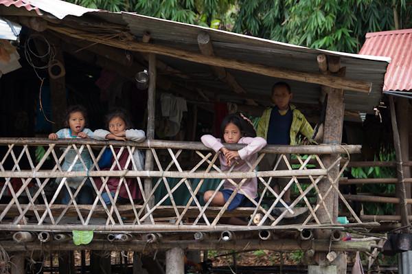 Niños Adi en la terraza de una casa de bambú en la aldea Kabu