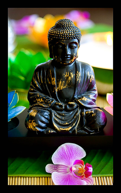 Buddha-Figur mit Orchideenblüten