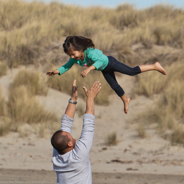 Love and Trust - Father tosses his confident daughter into to air accompanied by screams of delight.