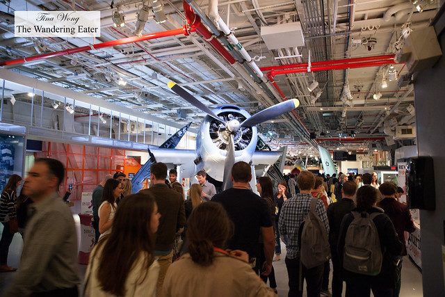Crowds eating and walking around these vintage war planes at the Hangar Section of the Intrepid Air & Space Museum