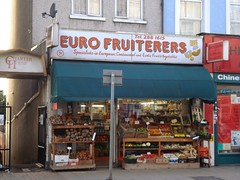 "A small grocery shop with open wooden shelves at the front holding vegetables such as yams, plantains, and chillies.  There is a small dark-green canopy above this.  A sign above the canopy reads ""Tel. 288 1615 / Euro Fruiterers / Specialists in European, Continental and Exotic Fruit & Vegetables""."