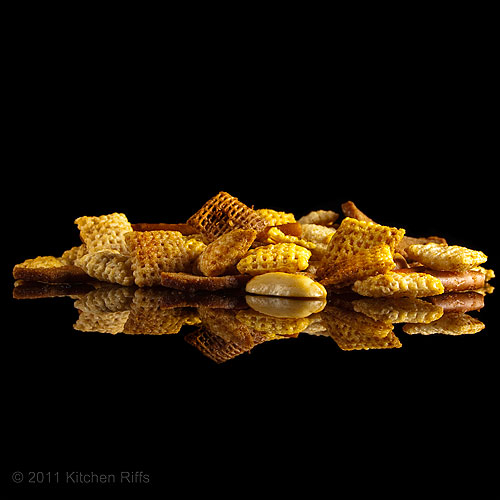 Homemade Chex Mix reflected on black acrylic