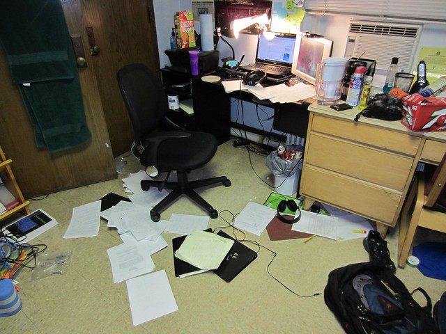 image of dorm room with belongings scattered all over desk and floor