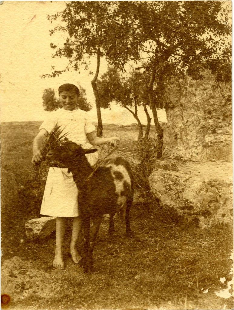 Niña alimenta una cabra a comienzos del siglo XX. Fotografía de Pedro Román Martínez. Centro de Estudios Juan de Mariana. Diputación de Toledo
