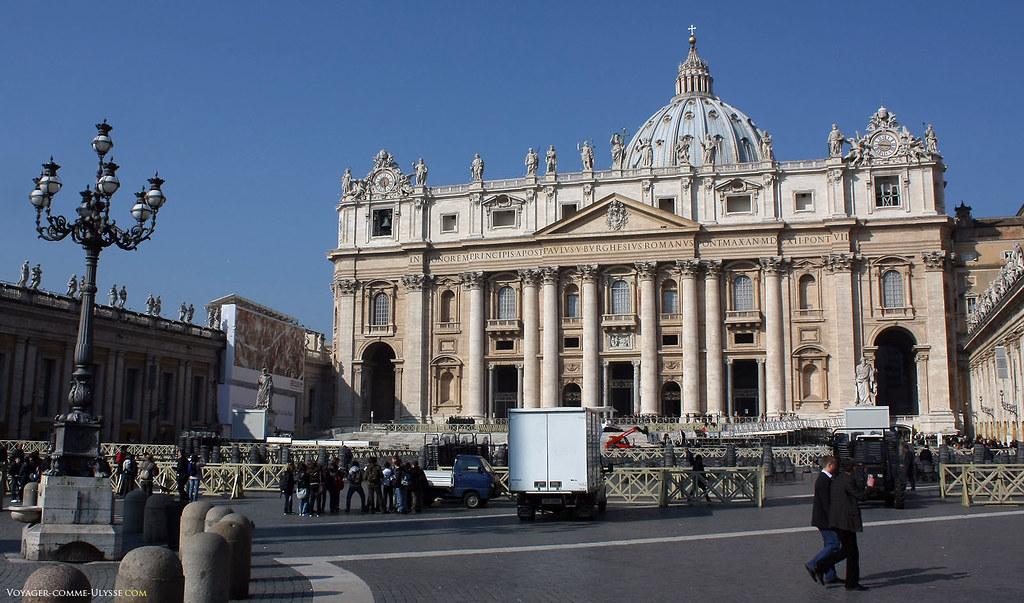 La façade colossale de la basilique, création de Maderno, cache le dôme. Le Christ est en haut, en plein centre, portant la croix. A chaque extrémité, les horloges de la basilique. Sous la cloche à gauche de la photo, on aperçoit une des cloches de Saint-Pierre.