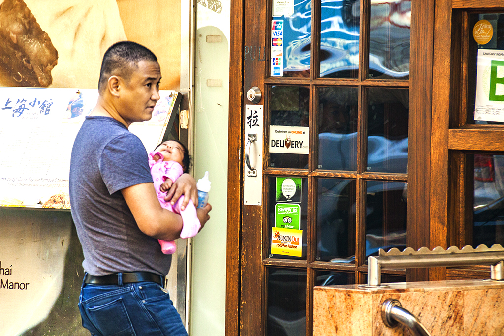 Man with baby and bottle outside restaurant--Chinatown