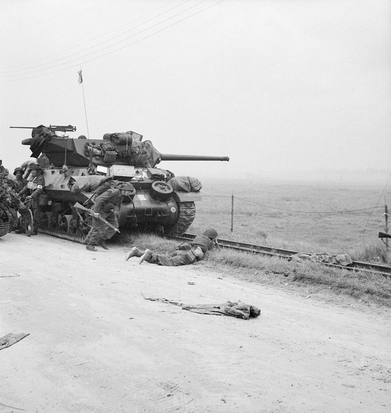 Troops take shelter near an M10 Wolverine tank destroyer.
